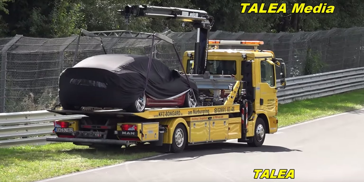 A Tesla Model S sat on a tow truck at the Nürburgring as a Porsche Taycan drove past it (TSLA)