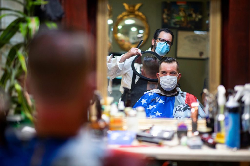FILE - In this Friday, June 26, 2020 file photo, Barber Mike McAndrew holds a mirror as customer Rob Verrastro looks at his new haircut at Three Saints Barbershop and Shave Parlor in Jessup, Pa. Restaurants, retailers and salons are desperately trying to stay afloat as the U.S. economy reopens in fits and starts after months in a coronavirus lockdown. But billions of dollars allocated by Congress as a lifeline to those very businesses are about to be left on the table when the government's Paycheck Protection Program stops accepting applications for loans Tuesday, June 29. (Christopher Dolan/The Times-Tribune via AP, File)