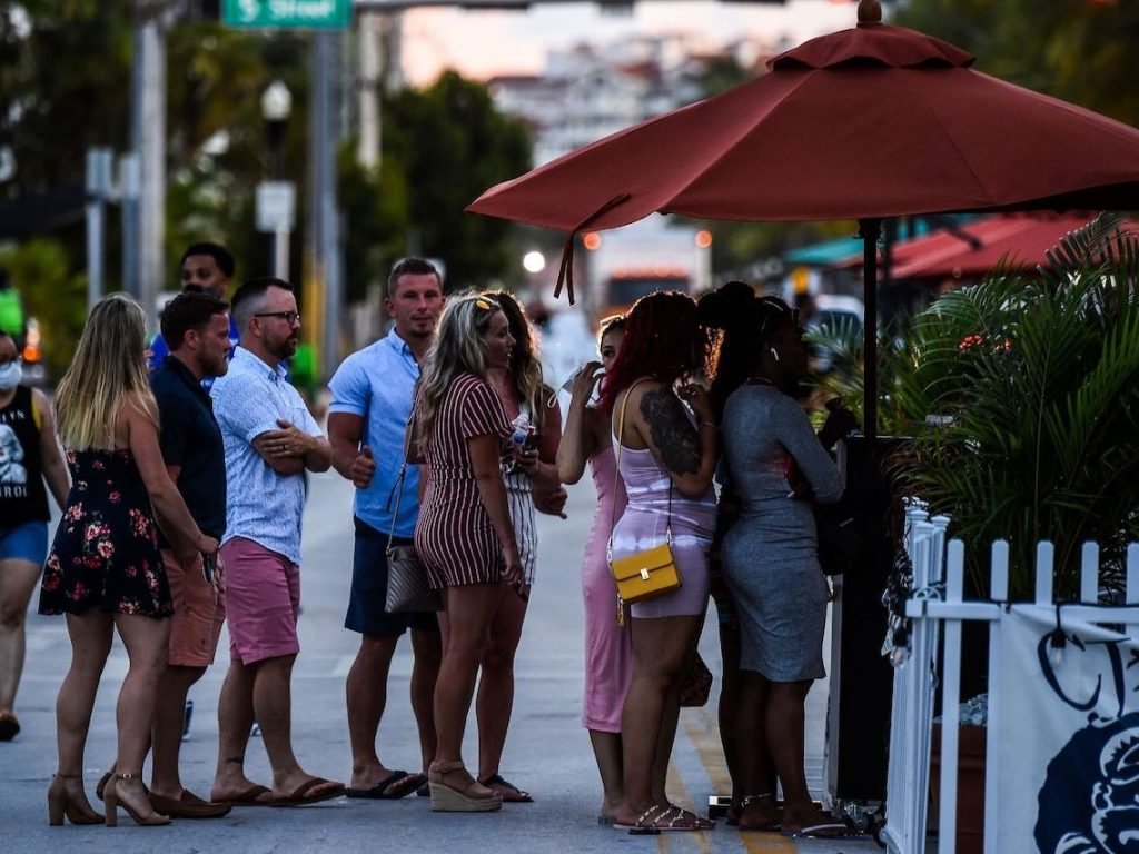 People stand in queue to enter a restaurant on Ocean Drive in Miami Beach, Florida on June 26, 2020.