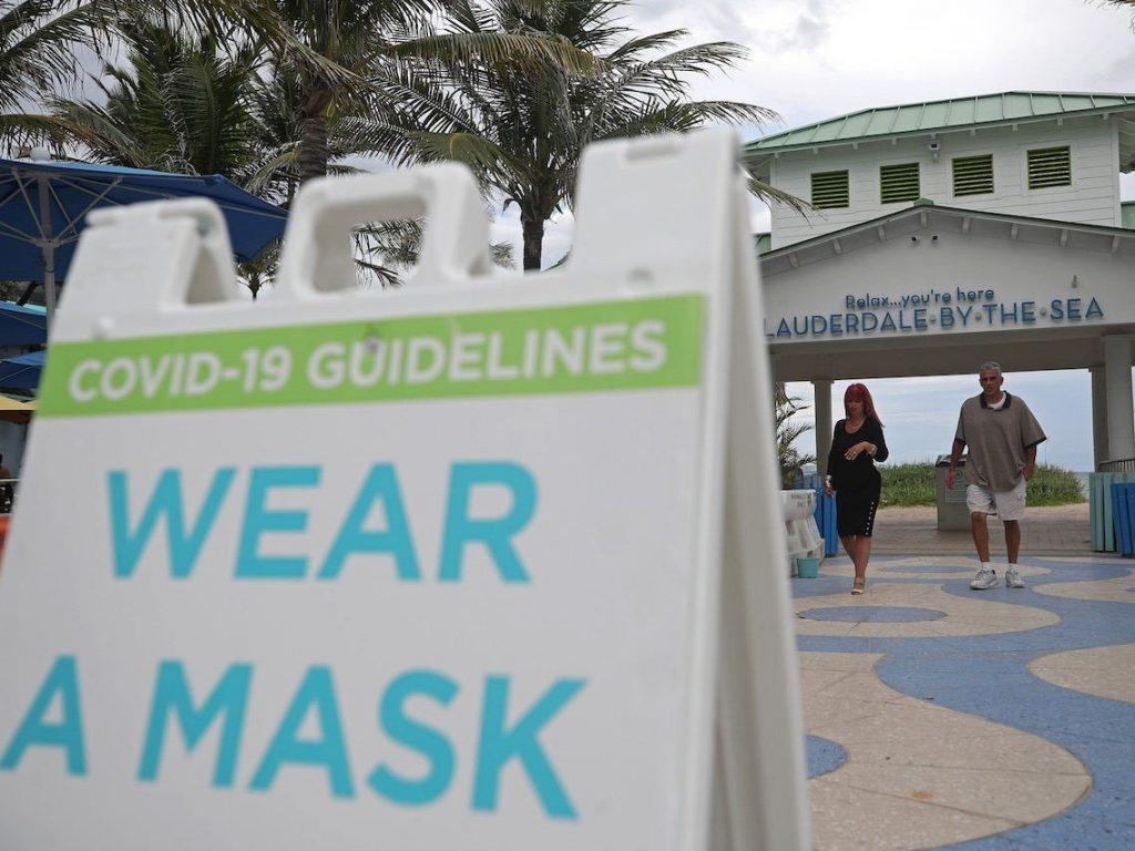 A sign alerts beachgoers to wear a mask near Anglin's Pier in Lauderdale-by-the-Sea on Wednesday, June 17, 2020.