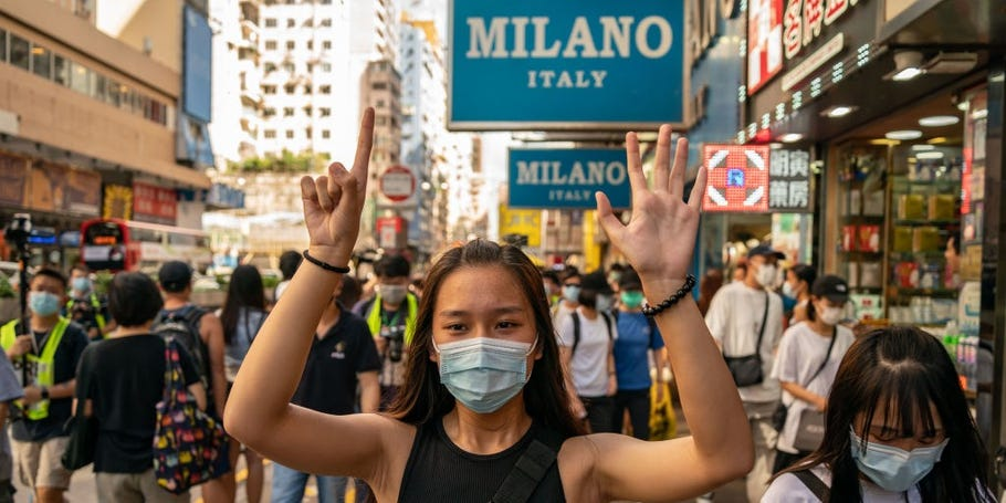 woman protests against hong kong security law with hand gesture