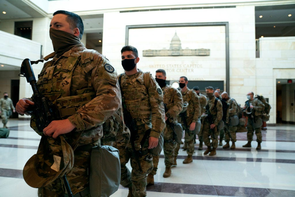Members of the National Guard walk through the Visitor Center of the U.S. Capitol on January 13, 2021 in Washington, DC.