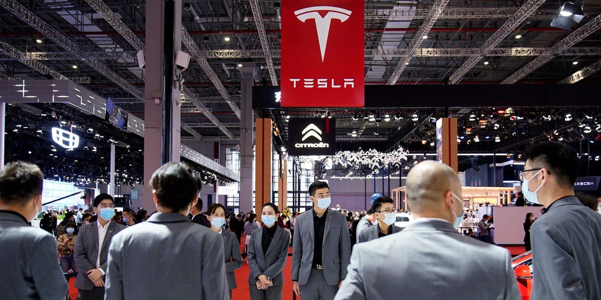Watch a disgruntled Tesla owner jump on top of a car at the Shanghai auto show (TSLA)